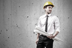 Architect at construction site holding plans. In front of a concrete wall Royalty Free Stock Photos
