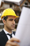 Architect in construction site looking at building plans Royalty Free Stock Photos