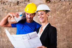 Architect and construction worker on site with plan Stock Photo