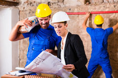 Architect and construction worker on site with plan Stock Photos