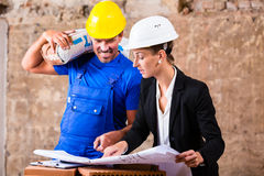 Architect and construction worker on site with plan Royalty Free Stock Images