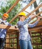 Architect And Construction Worker Working At Site. Architect and construction worker working on wooden frame at site Stock Photos