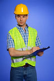 Architect in coveralls and hardhat using clipboard Stock Photo