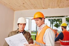 Architect and craftsmen working. Using floorplan for planning stock photography