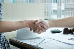 Architect and customer shaking hands at workplace. Engineer hand. Young architect and customer shaking hands at workplace. Engineer handshaking with partner for Stock Image