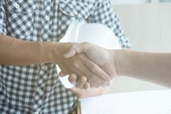 Architect and customer shaking hands at workplace. Engineer hand Stock Image