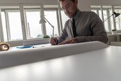 Architect, designer or draughtsman at work. In the office on a large blueprint or plan in a cropped low angle view across the table with copy space Royalty Free Stock Photography