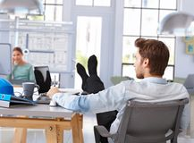 Architect designing with computer feet up on desk Royalty Free Stock Photos