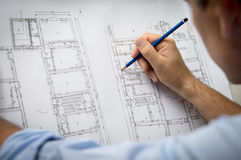 Architect Designing A New Building. Closeup Of Male Architect Working On Blueprint At Office Royalty Free Stock Image