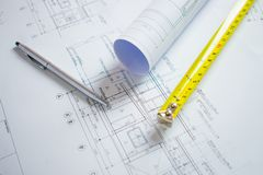 Architect desk with pen, meter cartridge on the blueprint for the house stock photography