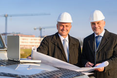 Architect developer hold construction plan. Male developers with blueprints at  construction site discuss architect project Stock Image
