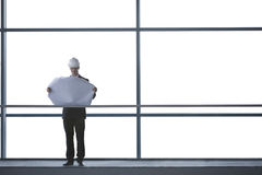An architect or developer standing on walkway of office building, looking at plans Stock Photography
