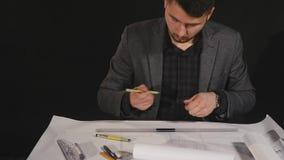 Architect die aan blauwdruk op zwarte achtergrond werken stock footage