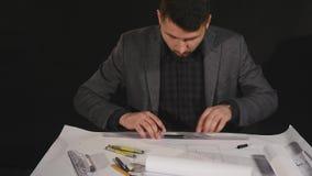 Architect die aan blauwdruk op zwarte achtergrond werken stock videobeelden