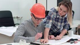 Architect die aan blauwdrukken werken terwijl vrouwelijke collega die meer tekeningen brengen stock video