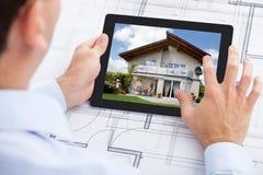 Architect die huis op digitale tablet over B analyseren Royalty-vrije Stock Foto's