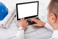 Architect die laptop in bureau met behulp van stock afbeelding
