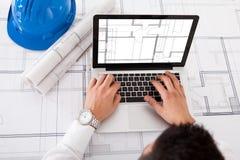 Architect die laptop in bureau met behulp van stock foto