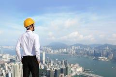 Architect die met helm de stadsbouw kijken Royalty-vrije Stock Foto's