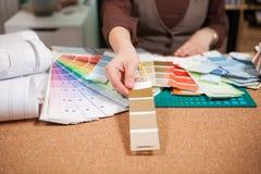 Architect die van verschillende kleuren op de kaarten kiezen Royalty-vrije Stock Afbeelding