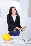 Architect with digital tablet standing at desk Royalty Free Stock Photos