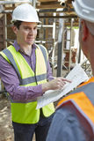 Architect Discussing Plans With Builder. Male Architect Discussing Plans With Builder Stock Photos