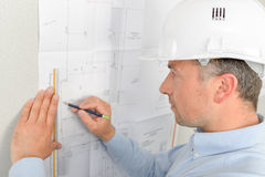 Architect drawing against wall Stock Image