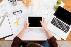 Architect drawing architectural project on tablet. Architect drawing on architectural project on digital tablet. Top view on unrecognizable designer hands Stock Photo