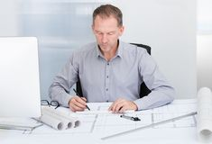 Architect drawing on blueprint Stock Photo