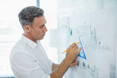 Architect drawing on blueprint at whiteboard Stock Images