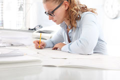 Architect drawing blueprints, at desk in office, with pencil Royalty Free Stock Images