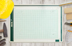 Architect drawing board surrounded by construction tools stock image