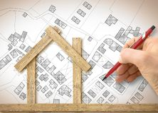 Architect drawing a conceptual wooden house over an imaginary cadastral map of territory with buildings, fields and roads -. Concept image royalty free stock photography