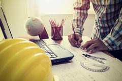 Architect drawing construction plan. With laptop in office Royalty Free Stock Images