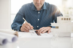 Architect drawing on a draft project. Professional architect working at office desk, he is drawing with a ruler on a draft project, architecture and engineering Stock Image