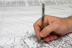 Architect drawing a plan. Architect checking the plan with a black ballpoint pen Stock Photography