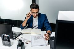 The architect dressed in a dark blue jacket works with documents on the desktop in the office royalty free stock photography