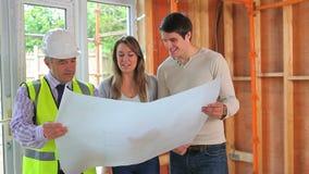 Architect en paar die het plan doorlezen stock footage