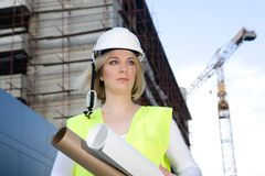 Architect or engineer. Young architect or civil engineer holding building plas at the constuction site royalty free stock images