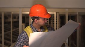 Architect or engineer checking construction site with plan. Concept: construction, worker, engineering, design stock video footage