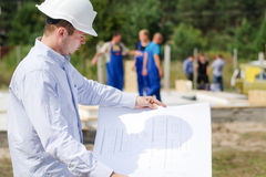Architect or engineer checking plans on site Stock Image