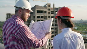 Architect and engineer discuss the project. Architect and engineer looking and discuss the development project on the construction site stock video footage