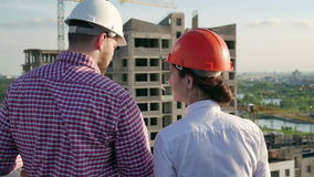 Architect and engineer discuss the project. Architect and engineer looking and discuss the development project on the construction site stock footage