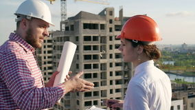 Architect and engineer discuss the project. Architect and engineer looking and discuss the development project on the construction site stock video