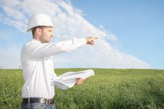 Architect engineer with drawings in white helmet pointing to site of construction site Royalty Free Stock Photo