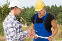 Architect or engineer explaining something. To a construction worker or builder pointing to a handheld document as they stand together on site Stock Photo