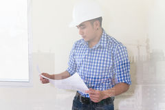 Architect or engineer man with blueprint and white safety helmet Stock Photography
