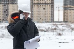 Architect, engineer, project manager or Senior engineer man talking on CB phone to building in the city with a blank. Plan as for construction. Soft focus Royalty Free Stock Photos