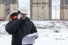 Architect, engineer, project manager or Senior engineer man talking on CB phone to building in the city with a blank. Plan as for construction. Soft focus Stock Photo