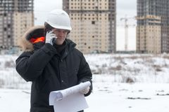 Architect, engineer, project manager or Senior engineer man talking on CB phone to building in the city with a blank. Plan as for construction. Soft focus Royalty Free Stock Image